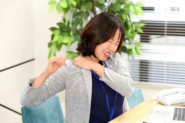 肩の痛みで腕を上げられずに悩む女性